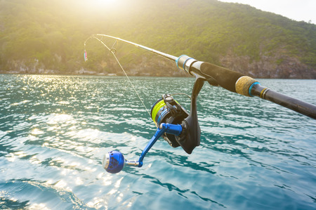 sea fishing: Fishing reel and sunrise at island Stock Photo