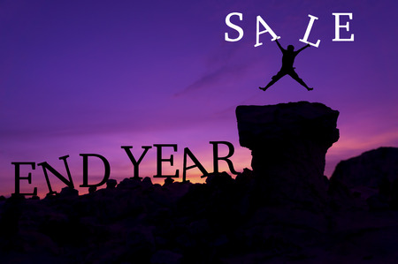 mount price: Silhouette man jumping on stone and holding word Sale - End Year sales concept
