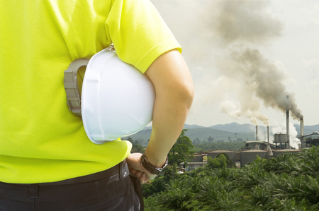 environmental issue: Safety and Health in workplace concept - Engineering man or Safety Inspector standing and looking to air pollution from palm oil mill