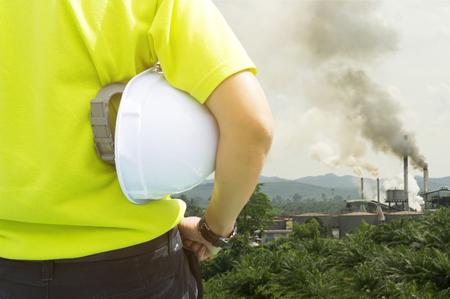 educacion ambiental: Seguridad y salud en el lugar de trabajo concepto - hombre de Ingeniería o inspector de seguridad de pie y mirando a la contaminación del aire de la fábrica de aceite de palma Foto de archivo