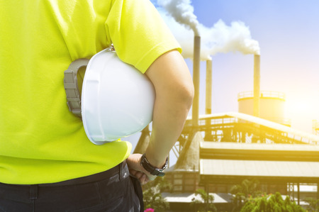 Veiligheid en Gezondheid in werkplaatsconcept - Techniekmens of Veiligheidsinspecteur die en zich aan luchtvervuiling van palmoliemolen bevinden kijken Stockfoto
