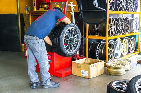 wheel balancing: JOHOR, MALAYSIA - DECEMBER 8, 2016 : Unidentified engineer balancing car wheel on balancer in workshop Editorial