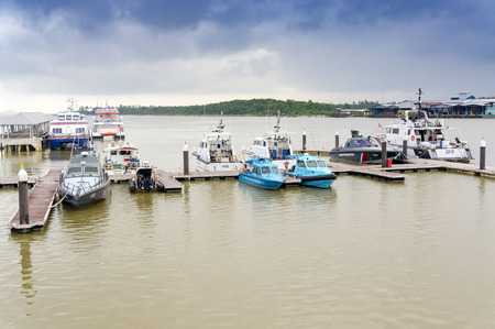 PAHANG, MALAYSIA - JANUARY 30, 2017: Boats and ferry anchored at the jetty during the monsoon season at Pahang, Malaysia. its one of the piers for tourists to the Tioman Island.