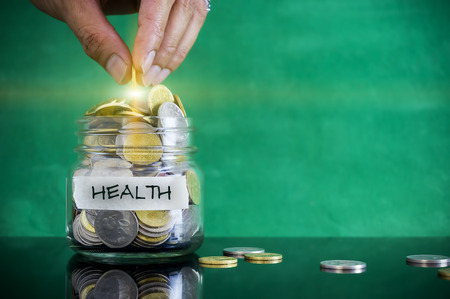 personel: Preparation for future and financial concept. Coins in glass jar with HEALTH label. Malaysia coins. Stock Photo