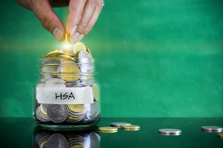 personel: Preparation for future and financial concept. Coins in glass jar with HSA (Health Saving Account) label. Malaysia coins. Stock Photo