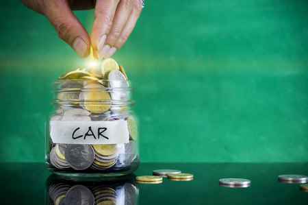 personel: Preparation for future and financial concept. Coins in glass jar with CAR label. Malaysia coins. Stock Photo