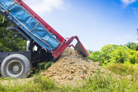 PAHANG, MALAYSIA - FEBRUARY 26,2017: Dumper truck unloading soil or sand at construction site at blue sky background Editorial