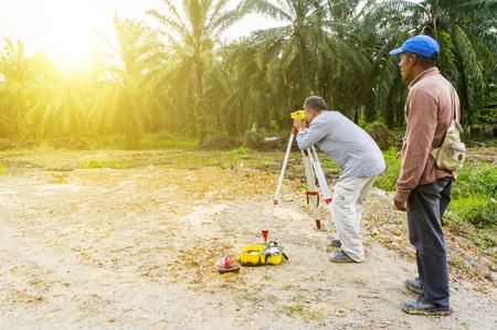 surveyors: PAHANG,MALAYSIA-FEBRUARY 27,2017: Unidentified surveyor is measuring level on new palm oil plantation. Surveyors ensure precise measurements land boundary for new plantation. Editorial