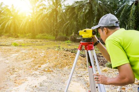 surveyors: PAHANG,MALAYSIA-FEBRUARY 27,2017: Unidentified Surveyor is measuring level on new palm oil plantation. Surveyors ensure precise measurements land boundary for new plantation.