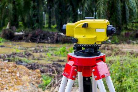 surveyors: Surveyor equipment tacheometer or theodolite on new palm oil plantation. Surveyors ensure precise measurements land boundary for new plantation.