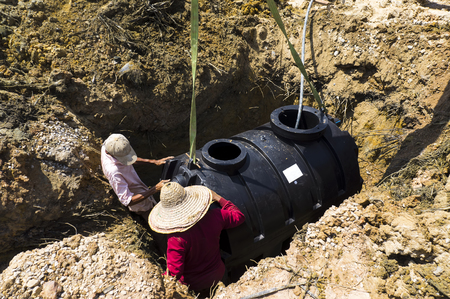 Septic tank installation in hole.