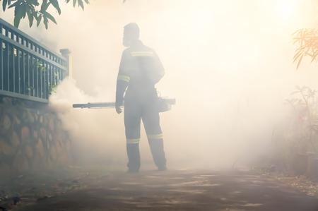Environmental health operator fogging using chemical for dengue controle uitbraak met zonlichteffect. Bewegingsonscherpte effect.