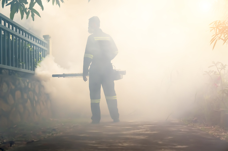 Environmental health operator fogging using chemical for dengue control outbreak with sunlight effect. Motion blur effect.