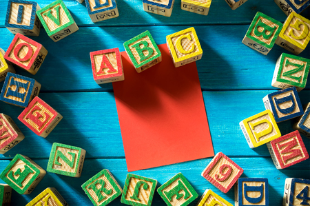 Close up arrangement of alphabet with sticky notes on blue background. Preschool, education concept or other your content. Long shadow and vignette effect.