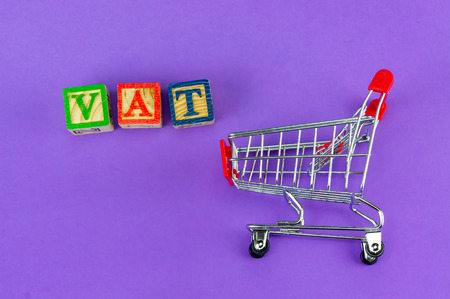 VAT (Value-Added Tax) on household goods concept. Trolley with alphabet (V.A.T) block on purple background. Standard-Bild