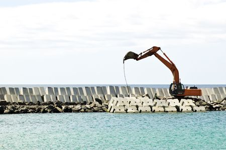 Heavy excavator machine in a pier construction site photo