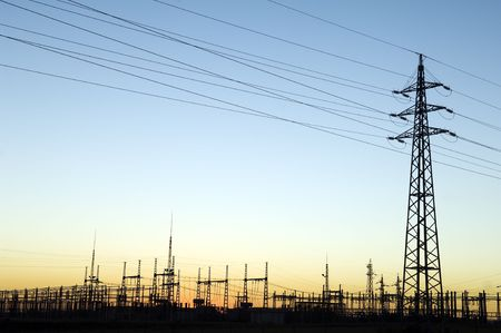 Power substation and pylon with distribution lines at sunset. photo