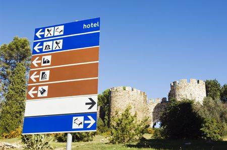 Signpost with blue, white an brown plates showing directions near a medieval castle, Portugal