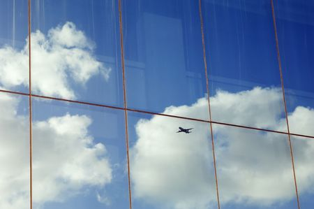 Airplane, sky and clouds reflected in the window of a modern office building