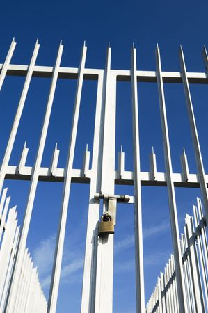 keep gate closed: Modern spiked fence and gate closed with a padlock Stock Photo