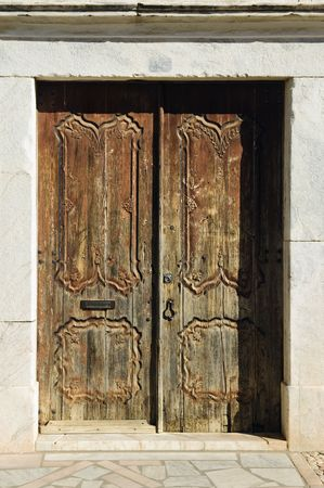 Ancient abandoned old door with nice woodcarvings  photo