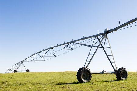 Resting irrigation pivot in a green grass field.