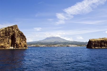 madalena: View from the sea of Pico Island, the volcano and the village of Madalena between two islets  Stock Photo