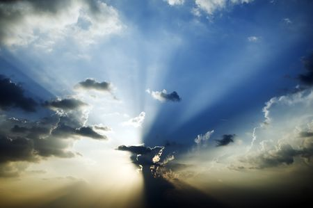 Sunburst in blue sky with beams shining through the clouds.