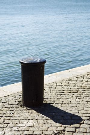 metal post: A view of a short, cylindrical metal post permanently attached to a pier or quay, often called a bollard to which a ship is tied while docked.