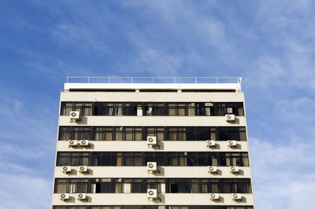 Drab, boring old building with air conditioning units in windows photo
