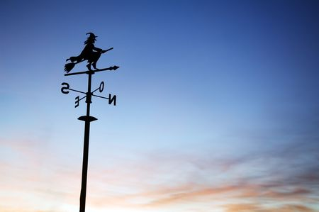 vane: A silhouette of a weather vane with a witch on top.  Stock Photo