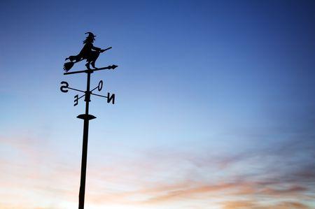 bruja: Una silueta de una veleta con una bruja en la parte superior.