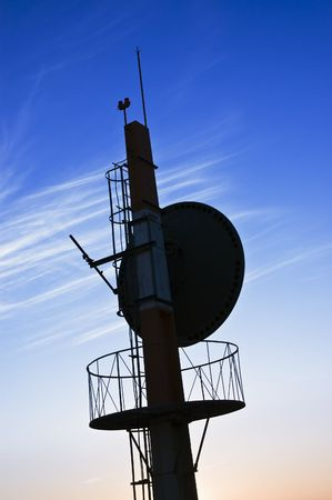 Telecommunications antenna against a clear blue sky photo