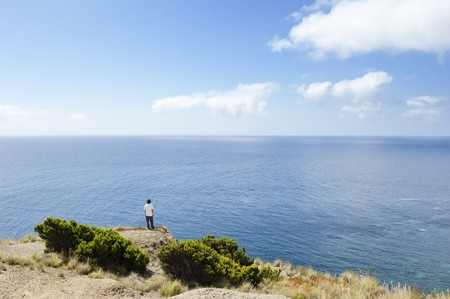 loner: Man at the edge of a cliff  looking at sea in Faial island, Azores, Portugal Stock Photo