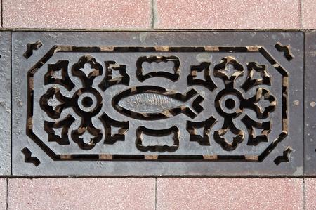 Decorated sewer grate in a street of Vila Real de Santo Antonio, Algarve, Portugal photo