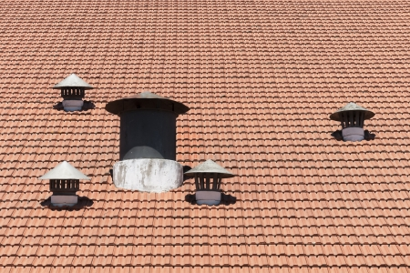 vents: Many air vents in a shingle red roof