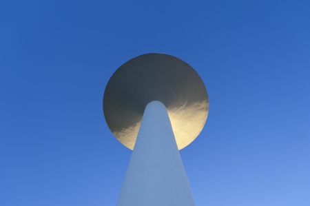 White painted water tower against a clear blue sky in the small village of S  Bartolomeu do Outeiro,  Alentejo, Portugal photo
