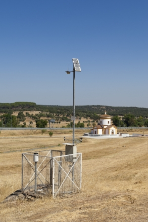 anemometer: Automated weather station in a field with a church in the background, near Monforte, Portugal Stock Photo