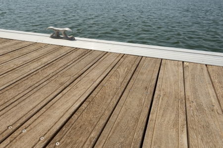 Detail of a wooden floating dock with mooring bitts