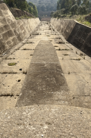 unattended: Concrete rundown overflow spillway in an old dam Stock Photo