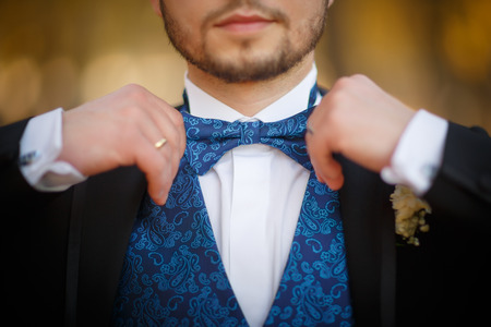 Bridegroom preparing for the wedding, corrects a beautiful bow-tie