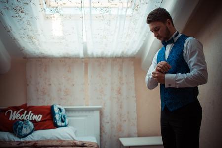 bridegroom: Bridegroom preparing for the wedding, straightens his shirt sleeves