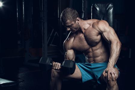 hombre: culturista masculino, modelo de la aptitud entrena en el gimnasio