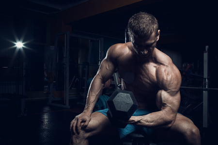 Male bodybuilder, fitness model trains in the gym Stock Photo