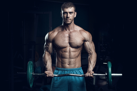 Male bodybuilder, fitness model trains in the gym 스톡 콘텐츠