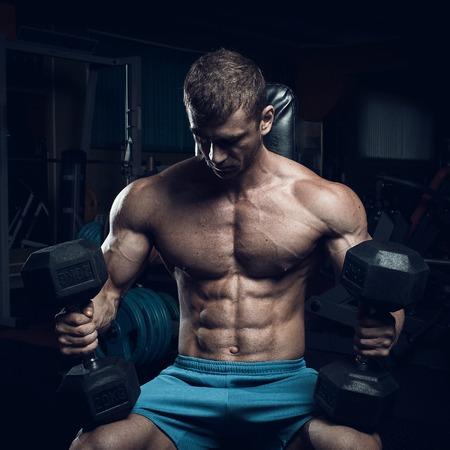 Mannelijke bodybuilder, fitness model traint in de sportschool
