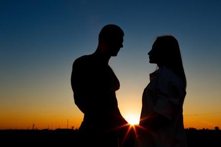 siluetas de mujeres: Siluetas de hombres y mujeres contra el fondo de una hermosa puesta de sol