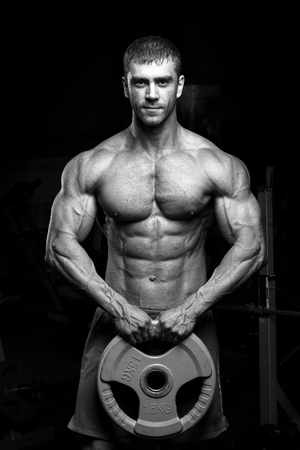 Male bodybuilder, fitness model trains in the gym. Black and white
