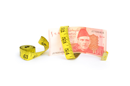 cutback: Closeup of hundred rupee Pakistani currency bill wrapped in measure tape for budget cut concepts Stock Photo