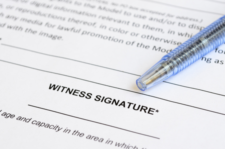 witness: Closeup of witness signature area on a document with artistic shallow depth of field.
